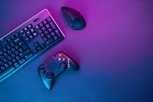 Keyboard, mouse and joystick on violet table background.